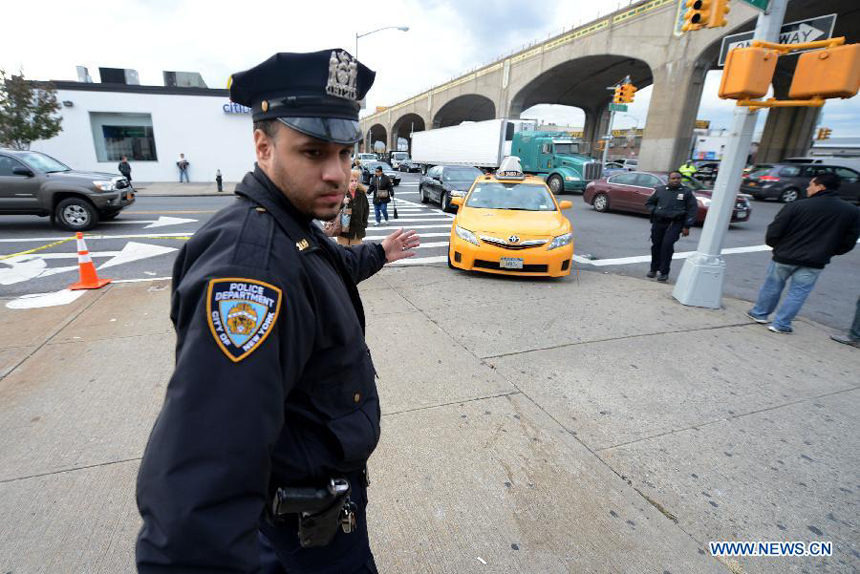 A policeman directs cars waiting to be refueled at a gas station in Queens, New York, the United States, Nov. 2, 2012. Four days after superstorm Sandy smashed into the U.S. Northeast, security measures were tightened up in New York as anger mounted over gasoline shortages, power outages and waits for relief supplies.