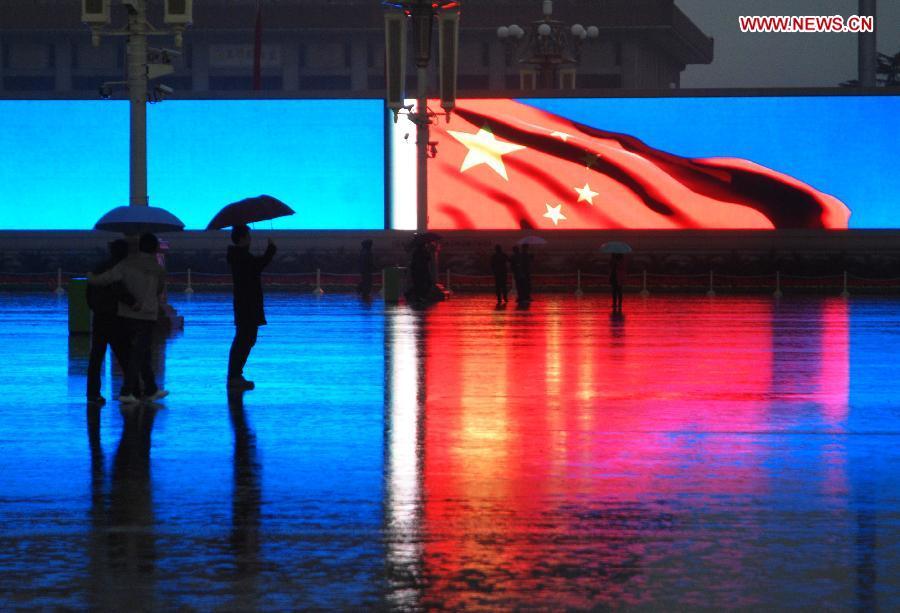 11月10日,游客们在雨中驻足观看天安门广场电子屏上滚动播放的宣传片《科学发展铸辉煌》。《科学发展铸辉煌》共有127张图片,分为经济篇、政治篇、民生篇、生态篇、文化篇、军队篇、一国两制篇、外交篇和党建篇,从多个角度反映党的十六大以来我国在各个领域取得的巨大成就,全片时长11分20秒,每天滚动播出30次左右。[新华社]