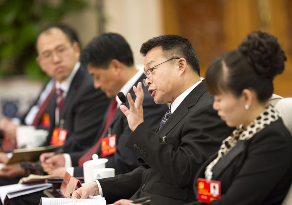 Hu Angang (2nd, R), president of the Institute for Contemporary China Studies of Tsinghua University, talks during a group discussion on the sideline on the sidelines of the 18th National Party Congress (NPC) in Beijing November 13, 2012. [Photo/Xinhua]