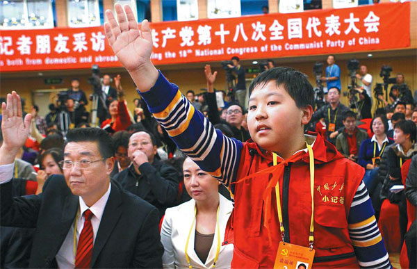 Zhang Jiahe, 11, a reporter from Chinese Teenagers News, attracts the attention of Minister of Housing and Urban-Rural Development Jiang Weixin during a news conference at the 18th Party Congress on Monday. He told the minister: 'Nowadays, houses are so expensive that many parents spend all their money on buying an apartment and even borrow lots of money from banks. They don't even have extra money to buy toys for their kids.' [Photo/China Daily]