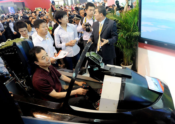 Astronauts Jing Haipeng (in the aviation simulator), Liu Wang (second left, second row) and Liu Yang (central, second row) try the aviation simulator of the Lieying L15 advanced trainer at the Ninth China International Aviation and Aerospace Exhibition in Zhuhai, Guangdong province, on Wednesday.[Photo/China Daily]