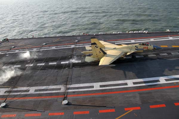 A J-15 fighter jet is slowed by an arresting device as it lands on the Liaoning aircraft carrier in a recent training exercise in Dalian, Liaoning province. [Li Tang / China Daily]