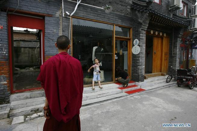 A little girl greets her Lama friend in front of her family's clothing shop in Wudaoying Hutong in Beijing, China, Aug. 30, 2011. This is one of Beijing's oldest Hutongs, yet it is also the city's newest trendy hangout.