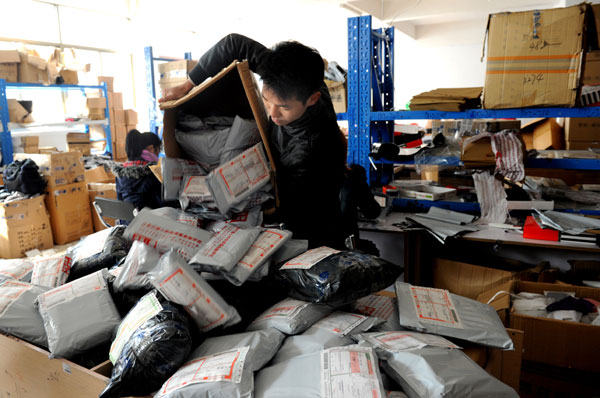 A worker at an online shop in Yiwu, Zhejiang province, sorts out parcels to be delivered this month.[Photo/China Daily]
