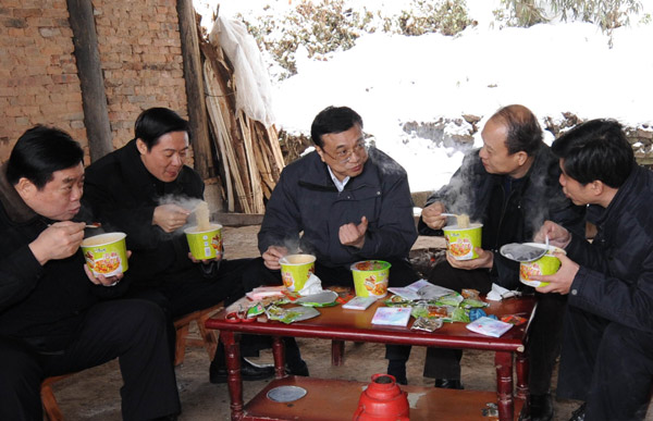 File photo taken on Jan. 31, 2008 shows Li Keqiang eats instant noodles with his colleagues as they talk about disaster relief work in the snowstorm-stricken Ziyun Village of Laojun Township of Xuanhan County in southwest China's Sichuan Province. [Photo/Xinhua]