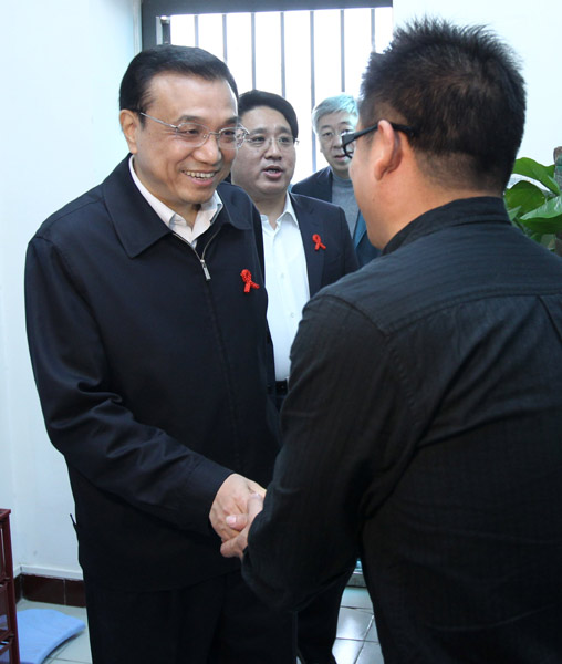 File photo taken on Nov. 18, 2011 shows Li Keqiang (L) shakes hands with an HIV carrier when he inspects AIDS prevention and treatment work in Beijing, capital of China. [Photo/Xinhua]