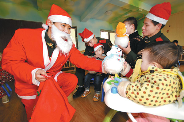 Soldiers don a different uniform as they bring joy to orphans in Taizhou, Zhejiang province, on Christmas Eve. [Photo/China Daily]