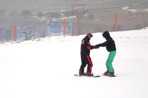 A coach helps a student learn the basics of snowboarding. [Photo: CRIENGLISH.com/William Wang]