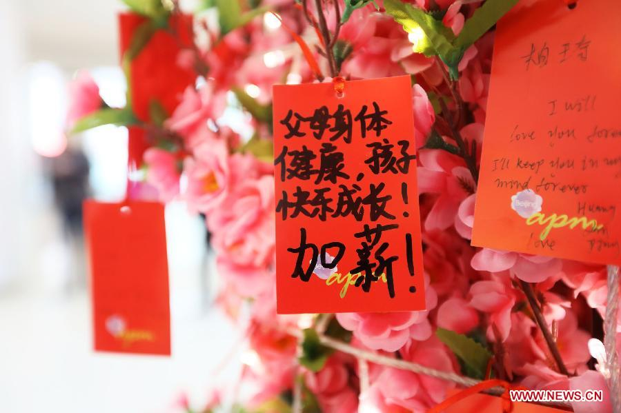 cards with peoples new year wishes written on them are tied to a wishing tree at