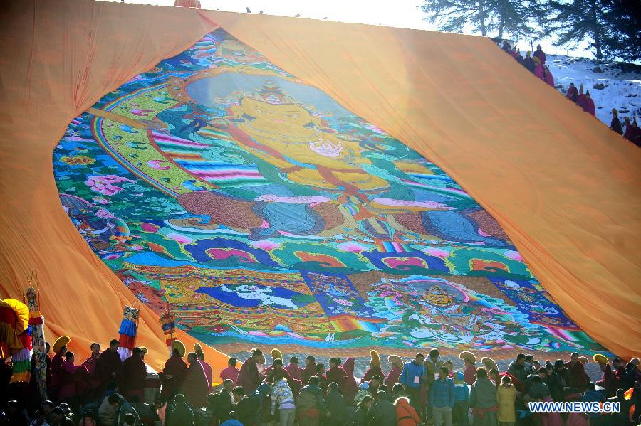 Lamas unveil a gigantic Buddha tangka alongside a hillside for disciples' worship in Labrang Monastery in Xiahe, northwest China's Gansu Province, Feb. 22, 2013.