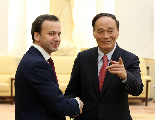 Vice-Premier Wang Qishan meets his Russian counterpart, Deputy Prime Minister Arkady Dvorkovich, at the Great Hall of the People in Beijing on Monday. They held talks on energy cooperation between the two countries. [Photo/China Daily]