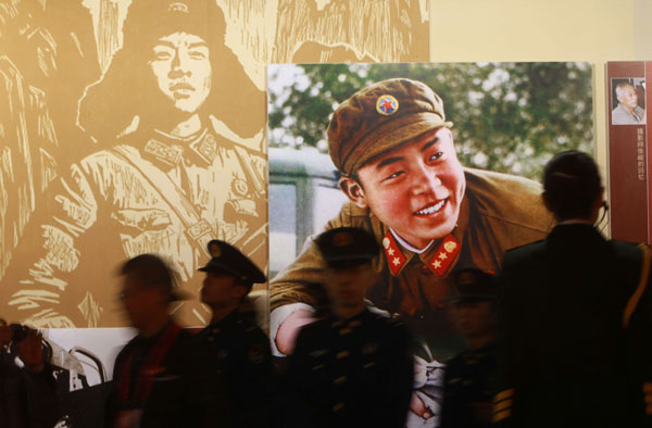 An exhibition, which opened on Monday at Beijing World Art Museum, showcases photos and audio material featuring Lei Feng. The young Chinese soldier, who died in 1962, is known for selflessly helping the needy. [Wang Jing / China Daily]