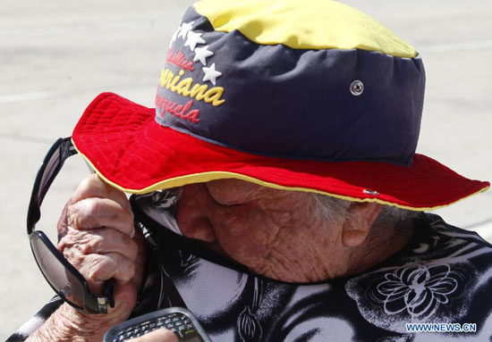 A resident reacts as he waits in the Proceres Avenue to enter the Military Academy of Venezuela to say his last goodbye to President Hugo Chavez, in the city of Caracas, capital of Venezuela, on March 9, 2013. [Xinhua Photo]