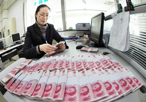 A clerk counts banknotes at a rural bank in Ganyu, Lianyungang city in Jiangsu province. A report by HSBC said China is likely to further widen the yuan's daily trading band and change the currency's fixing mechanism against the US dollar this year. [Photo/China Daily]