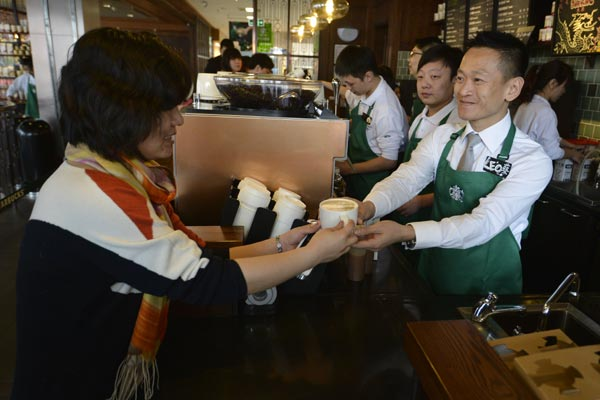 A customer receives her order at a Starbucks coffee shop in Taiyuan, Shanxi province. [Photo/China Daily]