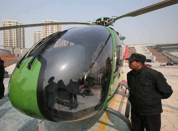 A visitor checks a helicopter on sale at a private aircraft store in Beijing on Saturday.[Photo/China Daily]