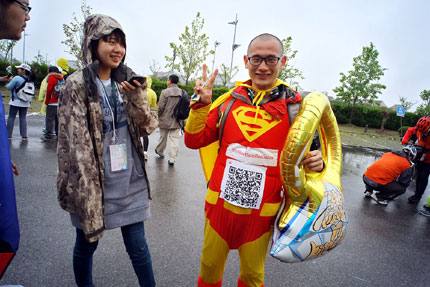 A man participating in the One Egg Project, a 50-kilometer charity walk, wears a costume emblazoned with the Superman symbol on Saturday. The project aims to provide poor children with one egg a day in their meal. More than 2,200 people took part in the event.