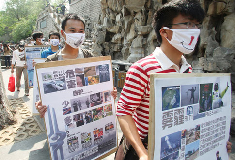 Students of Shandong Jianzhu University remind people of environmental protection by wearing masks and holding billboards on Sunday in Jinan, capital of Shandong province. China Daily