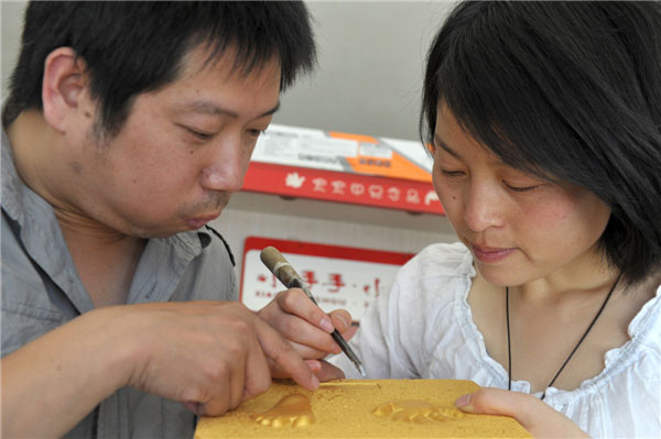The couple make hand and footprint products at their shop in Hefei, capital of East China's Anhui province on May 14, 2013. [Photo/Xinhua]