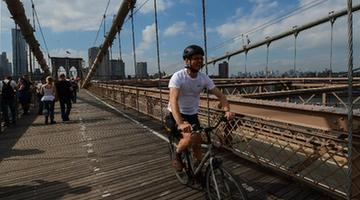 A man rides bicycle on the Brooklyn Bridge in New York, the United States, on May 20, 2013. The Brooklyn Bridge, opened on May 24, 1883, will celebrate its 130th birthday this week. (Xinhua/Niu Xiaolei)