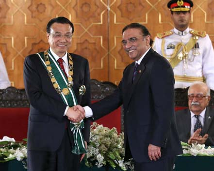 Premier Li Keqiang is congratulated by Pakistani President Asif Ali Zardari after being conferred the Nishan-e-Pakistan honor, for the highest degree of service to Pakistan, in Islamabad on Wednesday. [Pang Xinglei/ XINHUA]