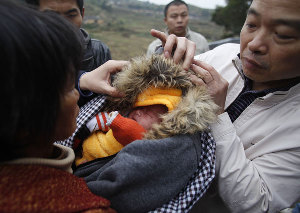 A woman holding a baby boy she bought from child traffi ckers is stopped by plainclothes police officers in Anxi county, Quanzhou, Fujian province, in December. [File photo]