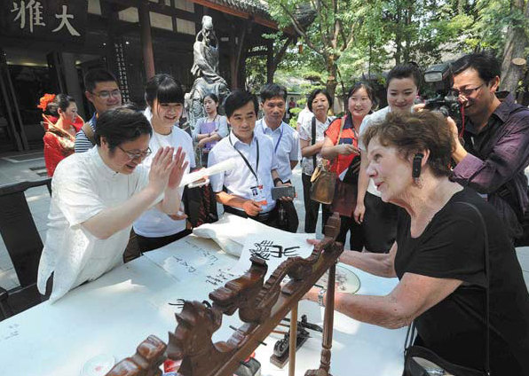 Local calligrapher Su Jiongshu composes a piece as a gift for an American guest who is the wife of a forum participant. [China Daily]