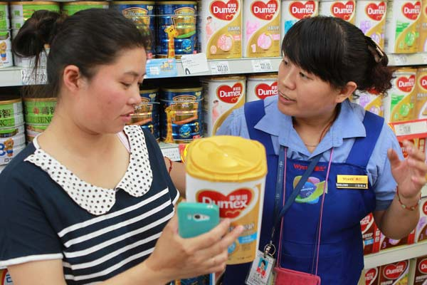Mu Liping (left) checks with a saleswoman at a supermarket in Beijing on Sunday whether her newly bought Dumex baby formula should be recalled. Dumex announced it was recalling 12 batches of products in China that may be contaminated. Mu found her purchase didn't belong to the recalled batches and left with the baby power.