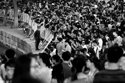 大量游客在大黄鸭前摄影留念,为防止意外,岸边设有防护栏,并配有武警把守。