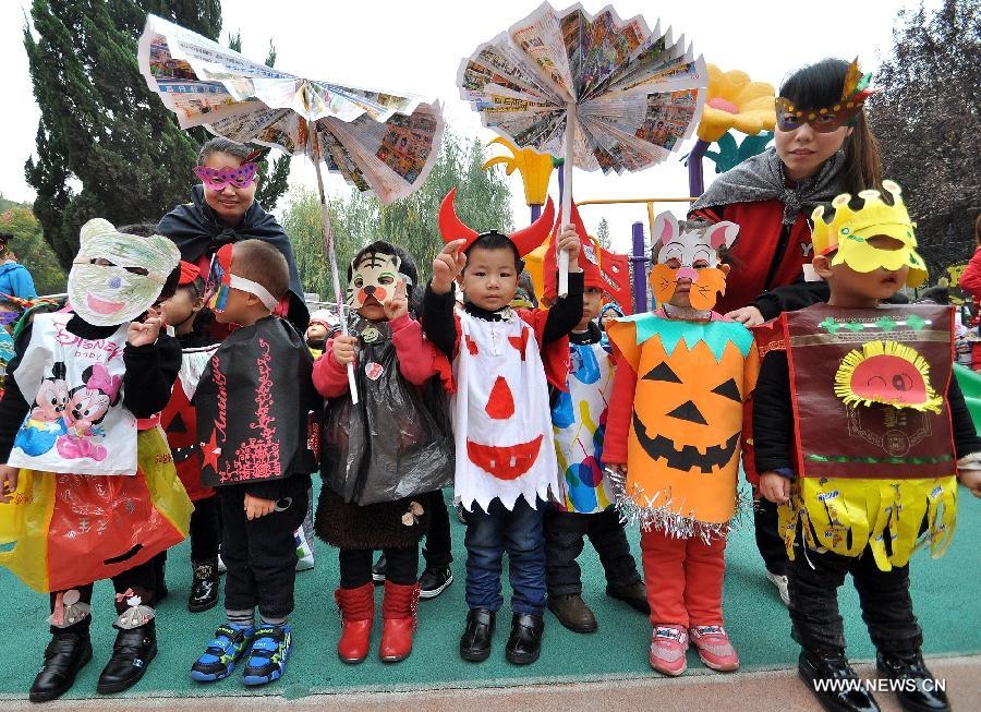 Teachers and children show costumes made with recycled materials to greet  the Halloween in a kindergarten