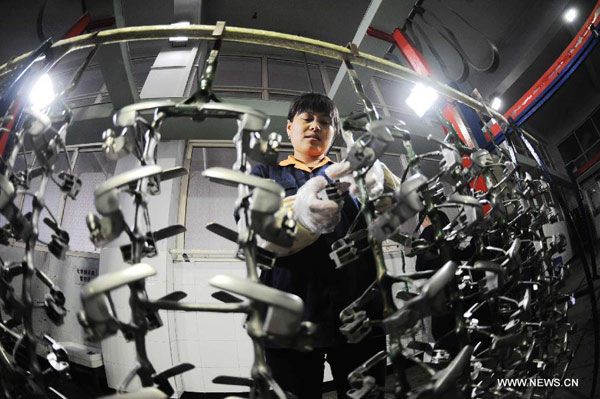 A worker of a company processes galvanized products in Qingdao, east China's Shandong Province, Nov. 1, 2012. [Xinhua/Yu Fangping]