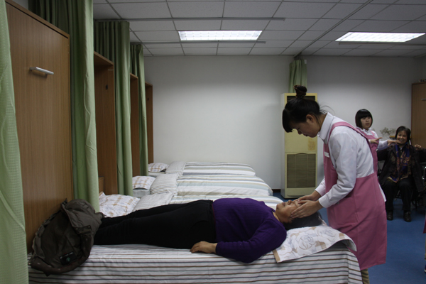 A nurse is massaging an aging visitor inside a club for the aging people in Jinrongjie Community. [Wu Jin/China.org.cn]