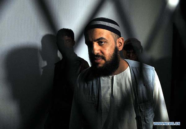 An al-Qaida suspect stands behind bars during a hearing at the state security court in Sanaa, Yemen, on Sept. 12, 2013. A Yemeni court on Thursday acquitted five Saudi nationals of links with al-Qaida, but jailed two of them for illegally entering the country, lawyers said. [Xinhua/Mohammed Mohammed]