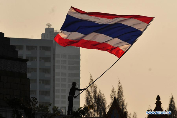 A Thai anti-government protester waves the national flag during a rally at the Victory Monument in Bangkok, Thailand, Dec. 22, 2013. Thailand's main opposition Democrat Party said it would boycott February's general election, deepening a political crisis as protesters called for another major rally Sunday to step up efforts to oust the government and force political reforms.[Xinhua photo]