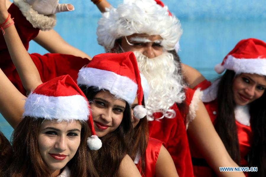young girls dressed in santa claus costumes pose for a photograph with santa claus during christmas eve celebrations at a water park in bhopal india - Do They Celebrate Christmas In India