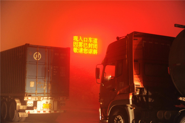 A digital sign reading 'the highway closed due to the haze' is seen near the entrance to Wuqiang county, Hengshui city of North China's Hebei province, on Shijiazhuang-Cangzhou Expressway, on the evening of Dec 7. Hebei province raised its smog alert to red on Dec 6, the highest level in the three-tier color-coded warning system. [Photo/Xinhua]