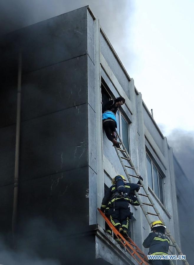 Rescuers try to save people trapped in a factory fire in Wenling, east China's Zhejiang Province, Jan. 14, 2014. A fire broke out at 2:52 p.m. in a shoe factory in Wenling City on Tuesday, leaving at least 16 people dead, the local government said. Firefighters are still searching for survivors. An initial investigation into the cause of the fire is under way. (Xinhua photo)