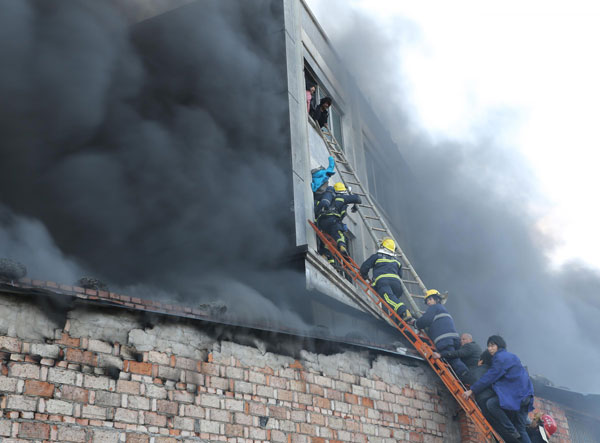 Firefighters work with local residents to rescue the workers trapped in a factory fire in Wenling city, East China's Zhejiang province, on Jan 14, 2014. [Photo/Xinhua]