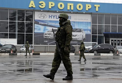 Unidentified armed men patrol outside of Simferopol airport, on February 28, 2014. Ukraine accused today Russia of staging an 'armed invasion' of Crimea and appealed to the West to guarantee its territorial integrity after pro-Moscow gunmen took control of the peninsula's main airport. [Xinhua photo]