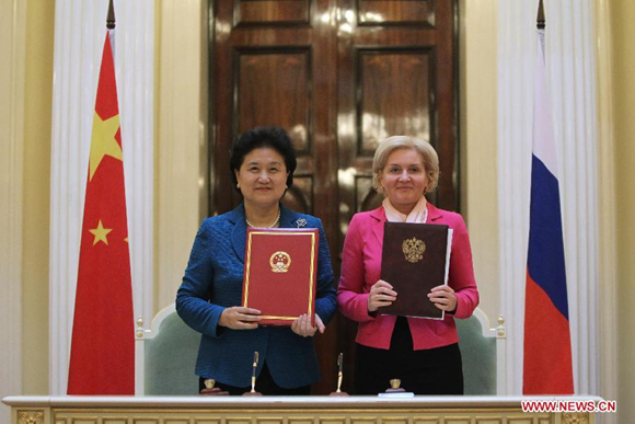Chinese Vice Premier Liu Yandong (L) and Russian Deputy Prime Minister Olga Golodets pose for a photo after signing a plan for a series of exchange activities in the coming two years in St. Petersburg, Russia, March 28, 2014. Liu Yandong and Olga Golodets co-hosted a joint meeting of the organizing committee of the China-Russia Youth Year of Friendship Exchanges on Friday. [Photo/Xinhua]