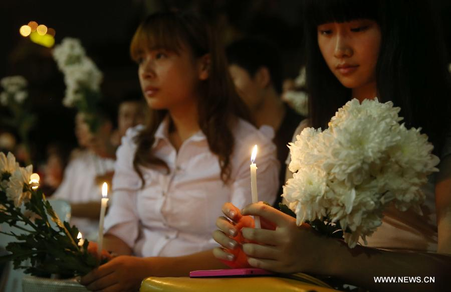 People hold candles and flowers to pray for the passengers aboard the missing Malaysia Airlines MH370 in Kuala Lumpur, March 30, 2014. [Xinhua/Wang Shen]