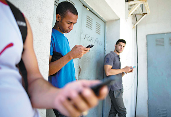 Students look for an Internet signal for their smartphones in Havana on Tuesday. [Photo/ China Daily via Agencies]