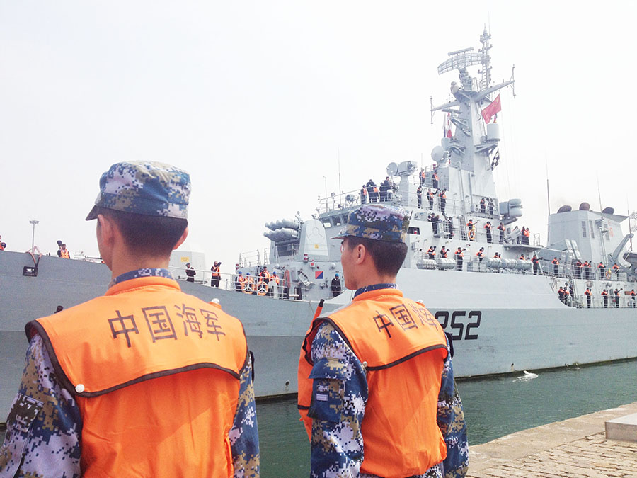 Chinese naval officers guard Pakistan's frigate Shamsheer, which arrived in Qingdao, East China's Shandong province, April 20, ahead of the 14th annual meeting of the Western Pacific Naval Symposium (WPNS), which the PLA's navy is expected to launch on April 22. [Photo/China Daily]