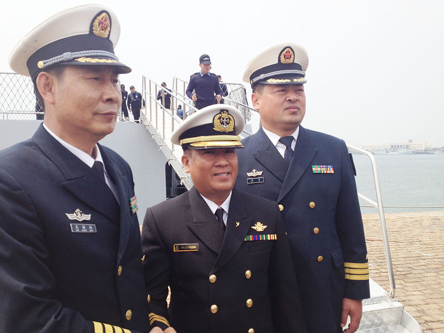 Willie Padan, commander of the Brunei patrol ship Darulehsan, poses for a photo with Chinese naval commanders upon his arrival in Qingdao, East China's Shandong province, April 20.[Photo/China Daily]