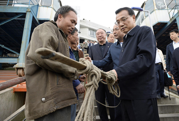 Chinese Premier Li Keqiang looks at a shoulder pole used by migrant worker He Shaoqiang during his inspection of the port's infrastructure and water channel conditions in Wanzhou, Chongqing Municipality, April 27, 2014.
