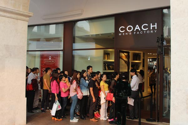 Customers line up to enter a Coach Inc store in Tianjin. [Photo/China Daily]