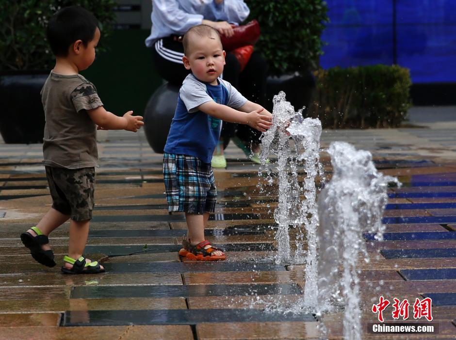 月26日,几名儿童在北京街头的喷泉边嬉戏。本周