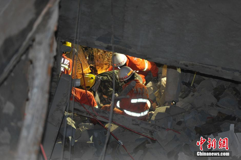Rescuers search for survivors at the site of a collapsed building in Taiyuan, capital of north China's Shanxi Province on September 21, 2014. A building under construction has collapsed there, trapping an unknown number of people. [Photo/Chinanews.com]