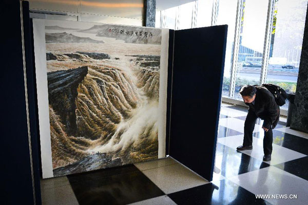 A man visits a Chinese art exhibition at the UN headquarters in New York Oct. 27, 2014. The Chinese art exhibition opened on Monday to present natural sceneries in China, with the 'preserve environment, cherish homeland' theme. [Xinhua]