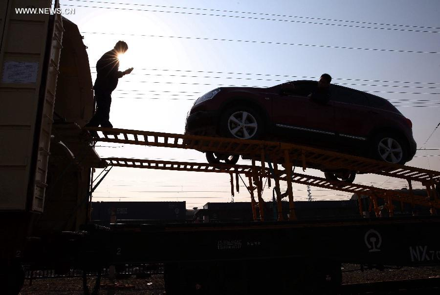 Workers load a car onto a carriage at Dahongmen Railway Station in Beijing, capital of China, Nov. 4, 2014. Beijing Railway Bureau has opened several special train routes for self-driving tourists during the vacation of the Asia-Pacific Economic Cooperation (APEC) Economic Leaders' Week, which will be held in Beijing from Nov. 5 to 11. [Photo/Xinhua]